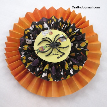 Create a black widow paper rosette with orange and black strips of Halloween paper. By Crafty Journal.